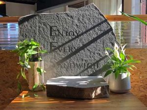 Slab of rock etched with text: Enjoy Every Sandwich